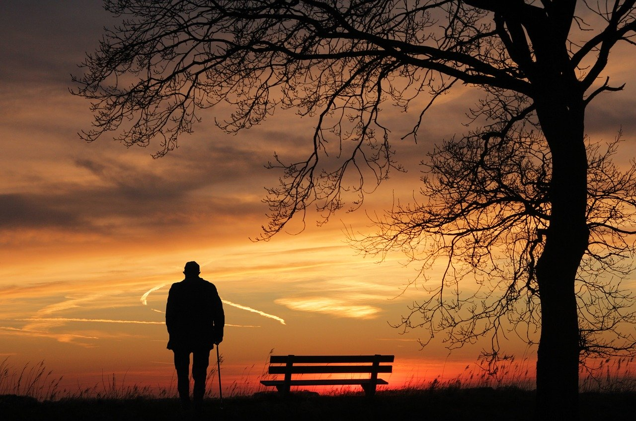 image of a lonely man watching the sunset